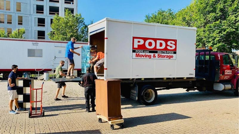 Men loading a PODS storage container on a parked truck