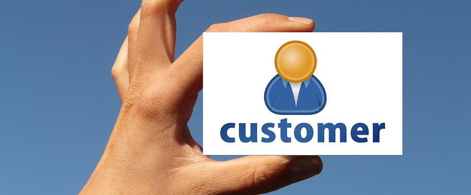 """A hand holding a card saying """"Customer"""""""
