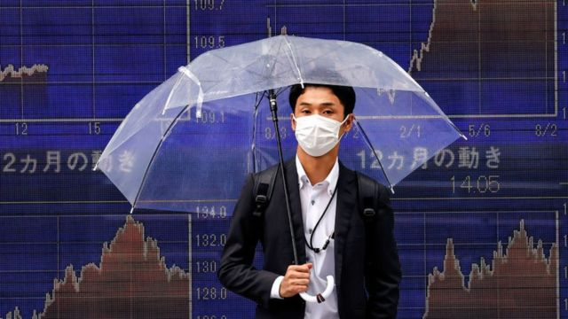 Main holding umbrella in front of stock market charts in Tokyo.