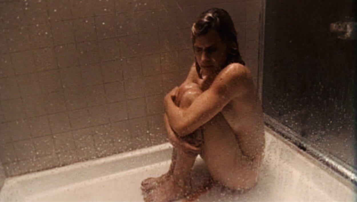 Sera cradles her knees and cries alone in the shower bleeding