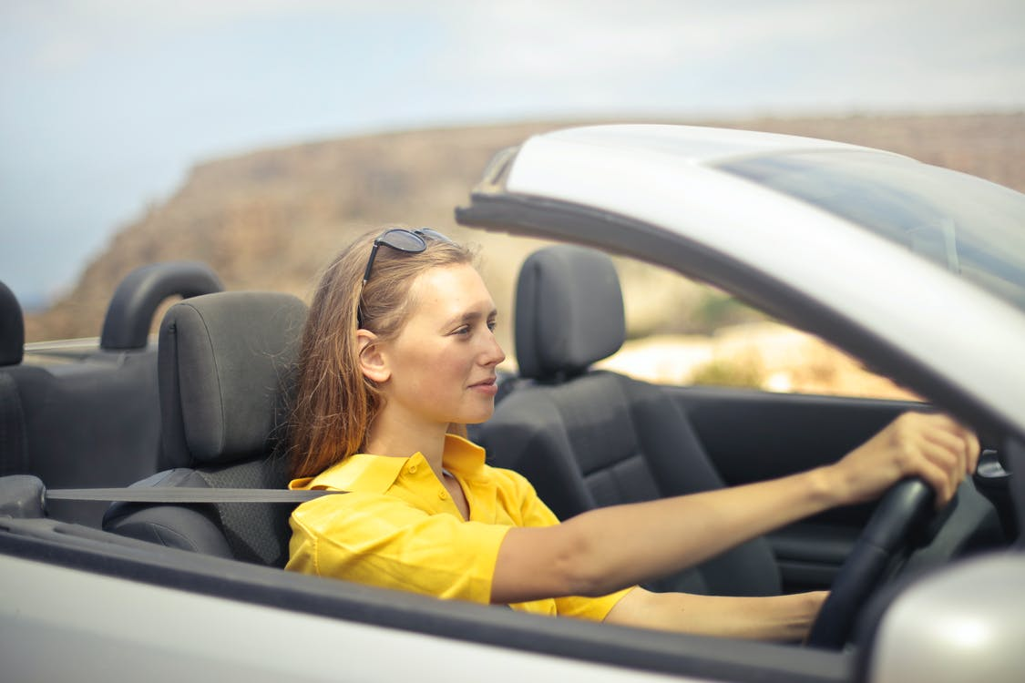 Woman in Yellow Shirt Driving a Silver Car