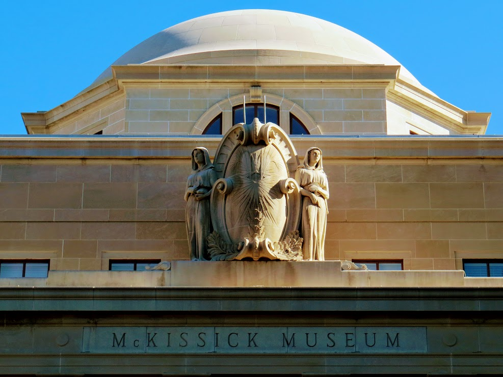 Color photo of statues on top of McKissick Museum