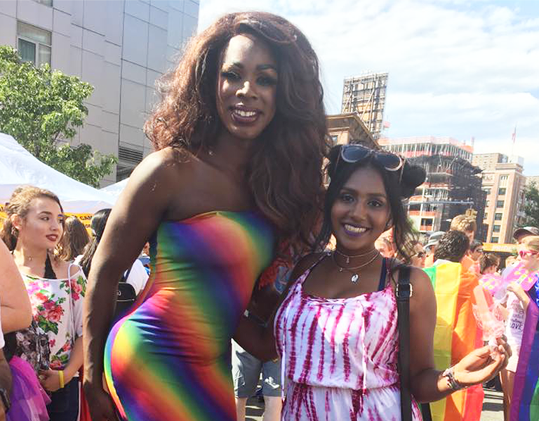 An au pair stands next to a drag performer at a pride parade in New York City.