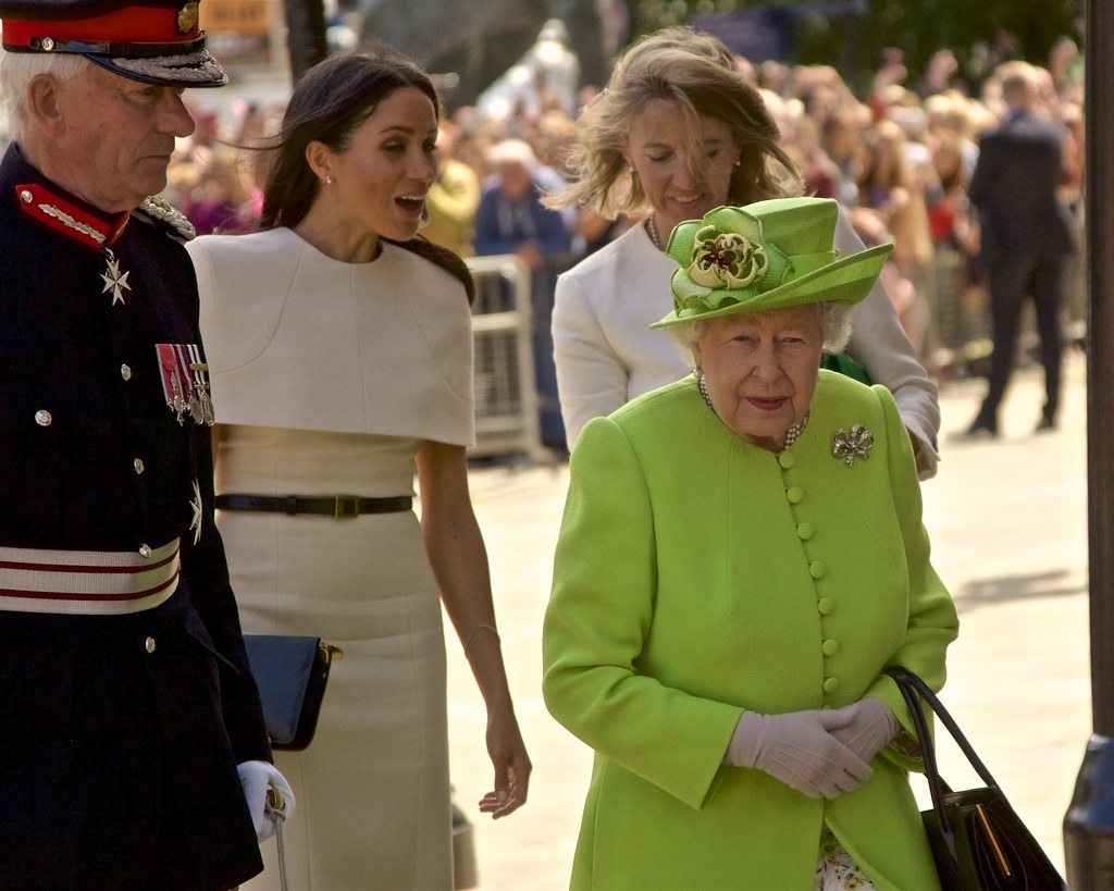 Meghan walks behind the Queen of England amid conversation with another woman.