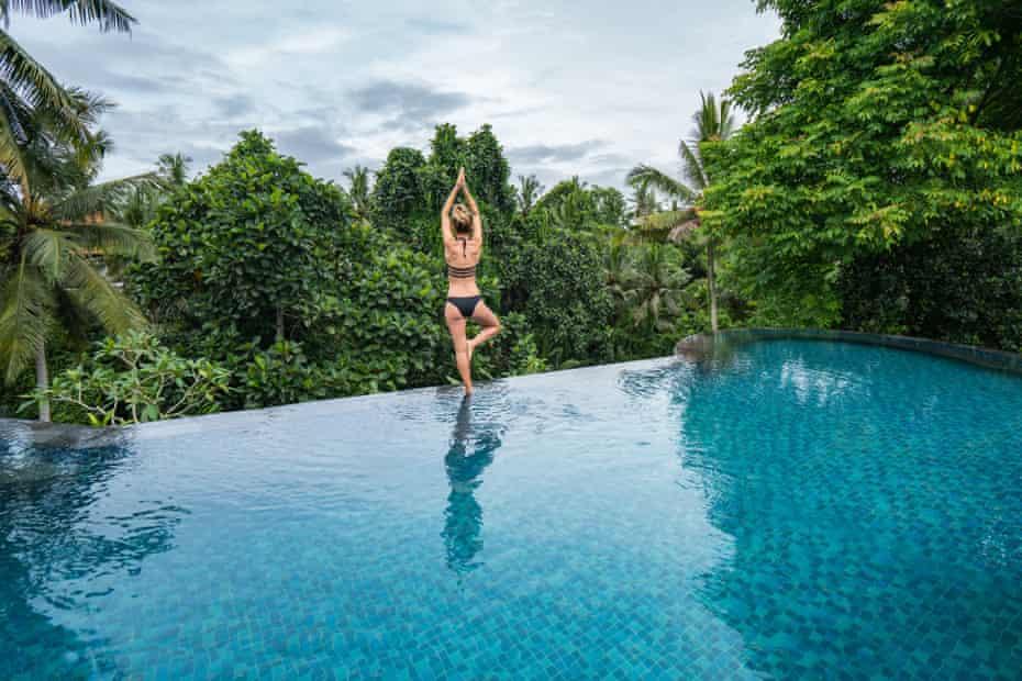 Young woman standing on the edge of an infinity pool, Ubud, Bali.