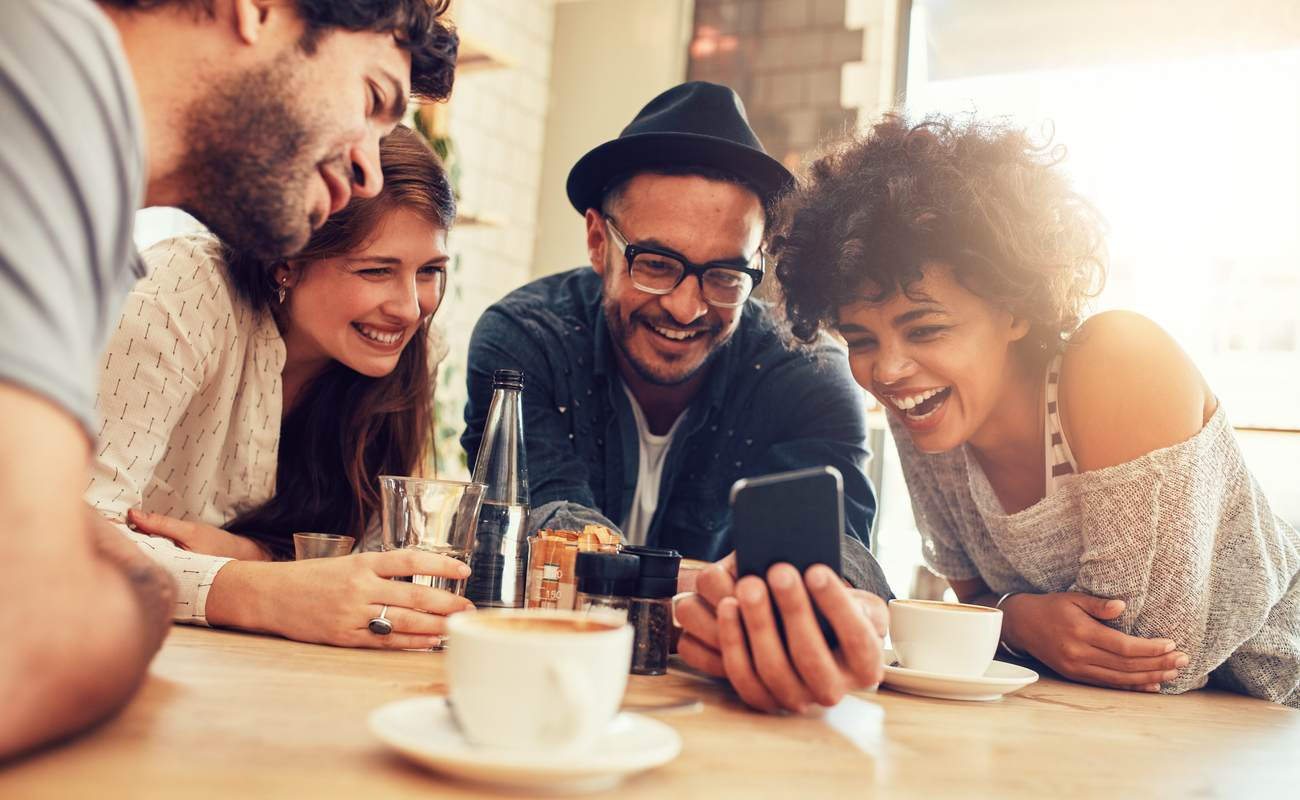 Cheerful friends looking at a smartphone while sitting in a cafe