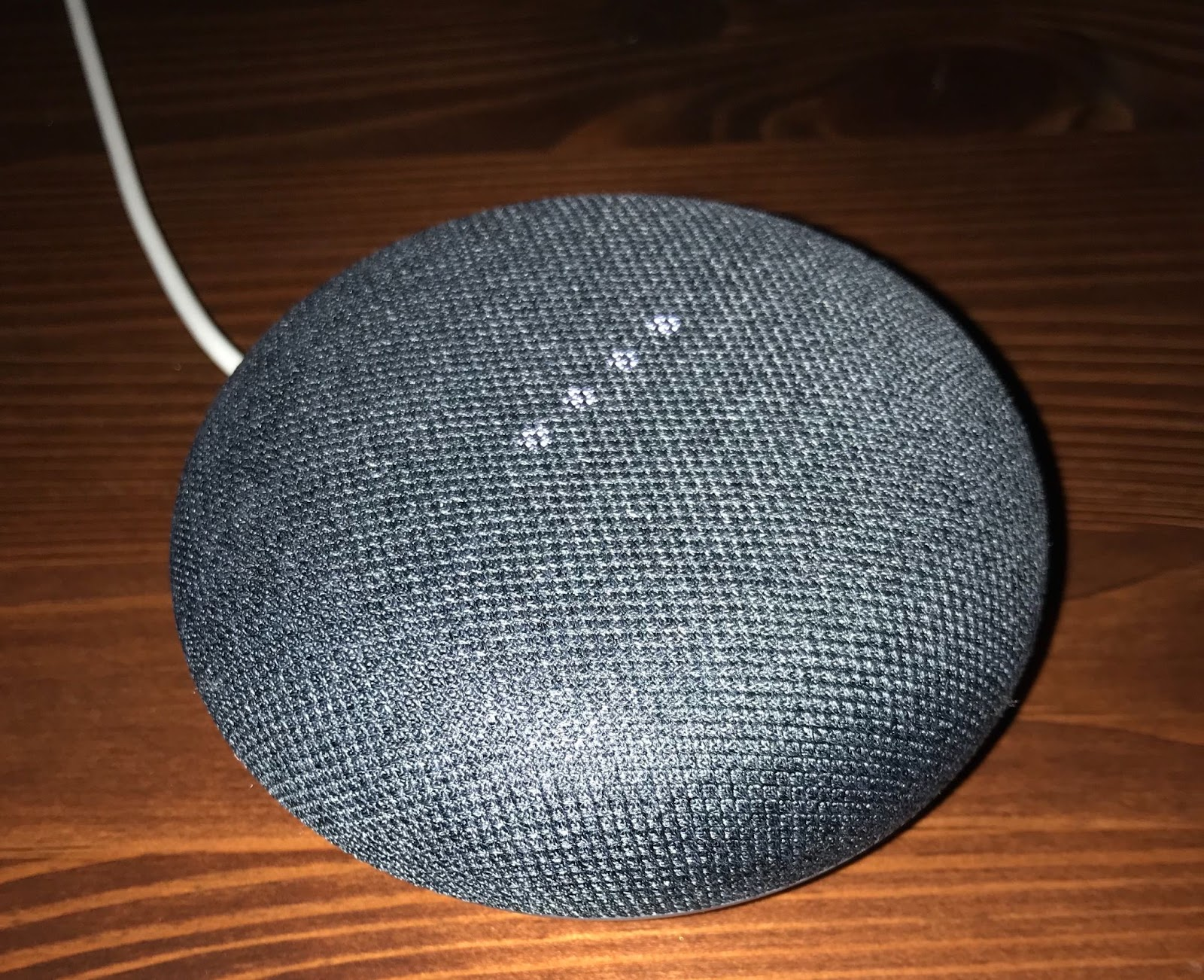 Gray First Generation Google Home Mini connected to a socket and lit LED lights in the middle