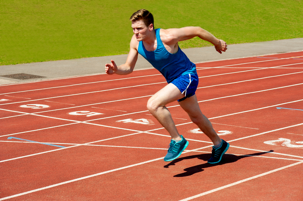 A person running on a track field.