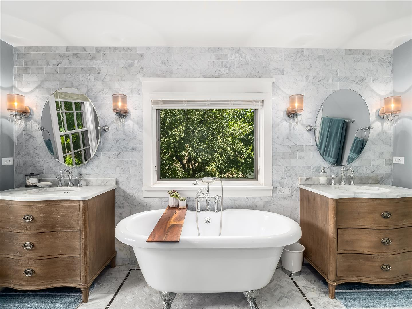 Claw foot tub under a picture window, flanked on either side by a single sink vanity.