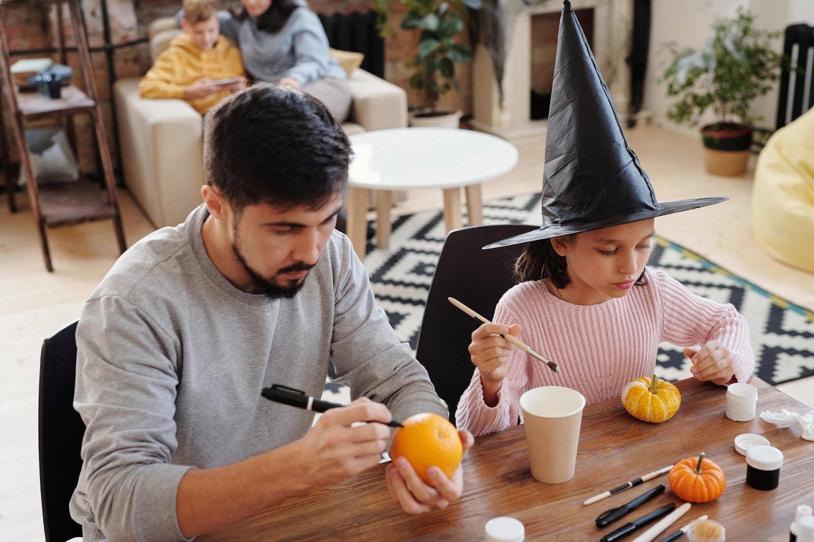 Man and child painting pumpkins as a fun autumn activity.