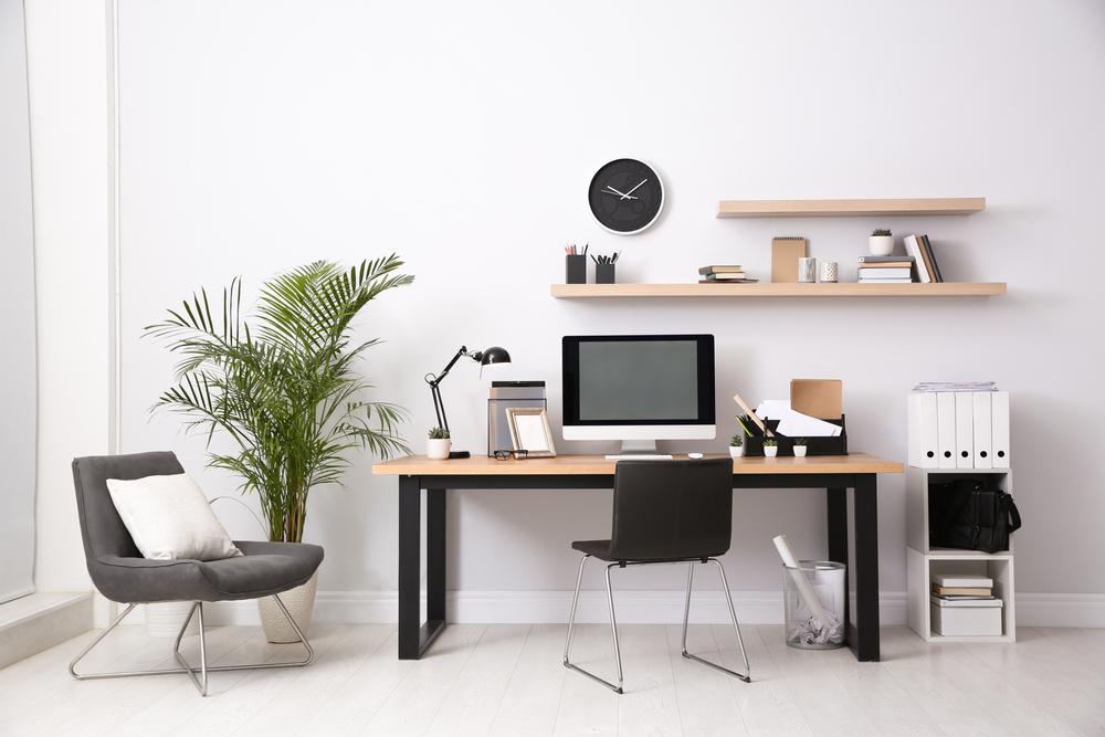 Um cantinho de home office com prateleiras, mesa e duas cadeiras bem decorados.