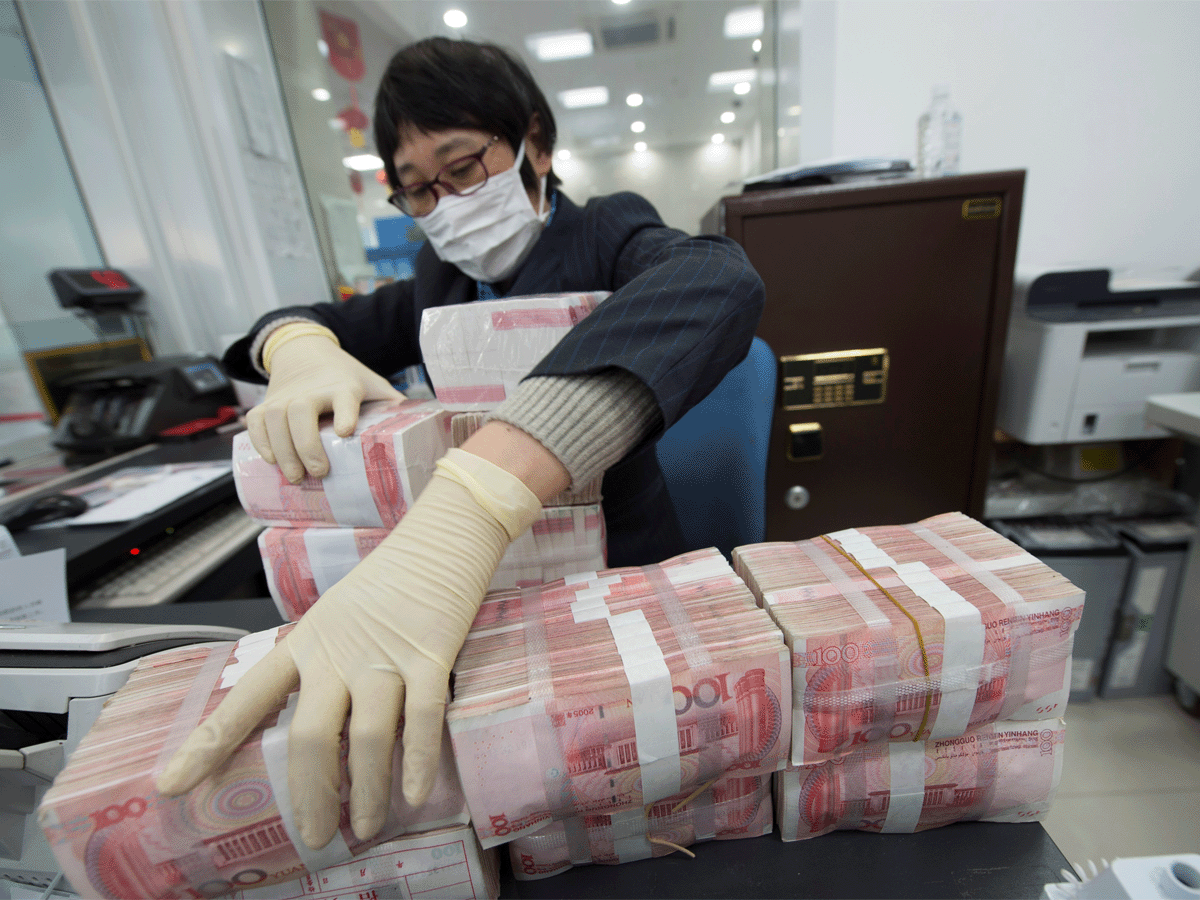 A Chinese official cleans banknotes to prevent the virus from spreading during the coronavirus outbreak.