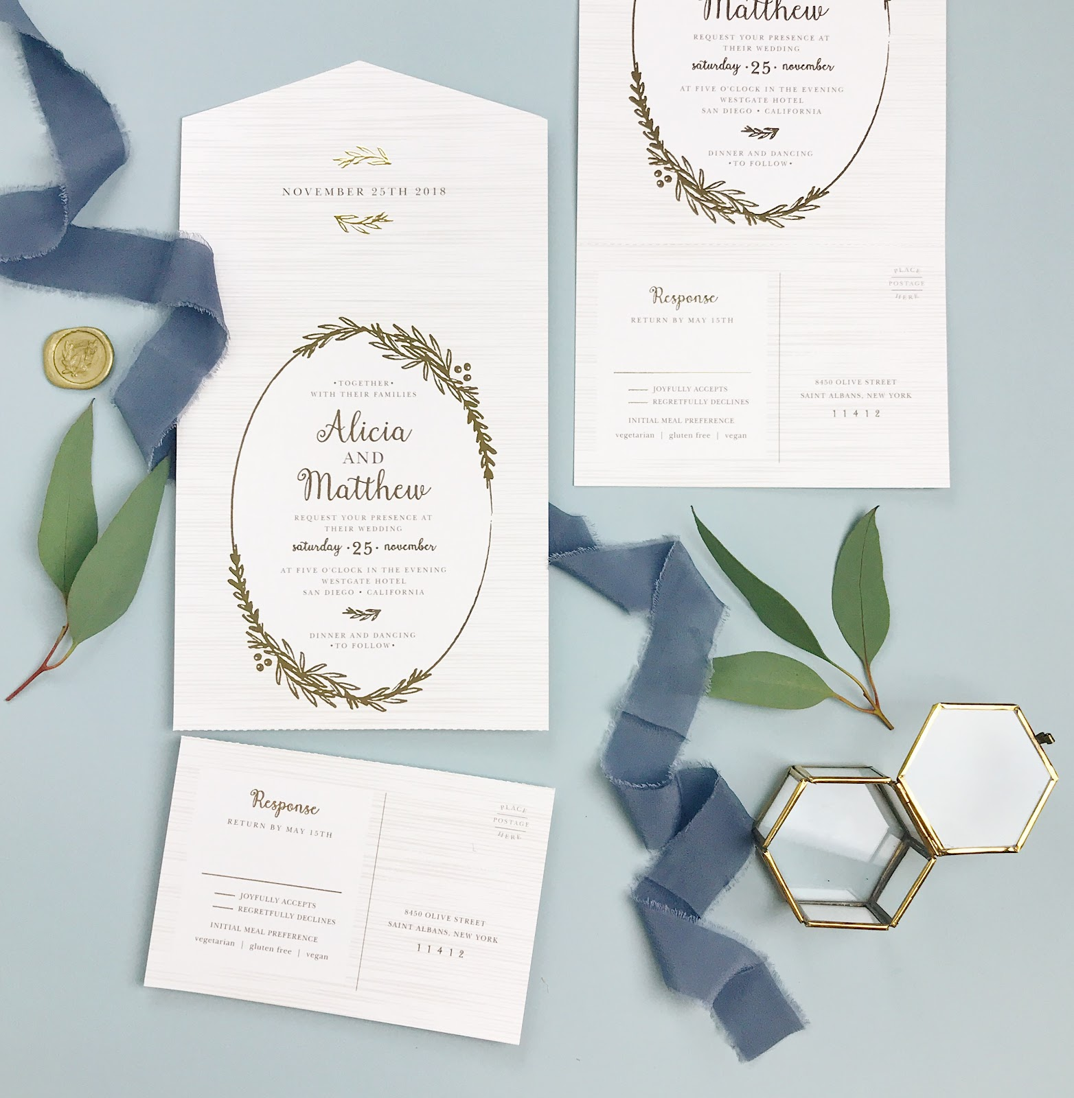 Dusty blue backdrop with gold no envelope wedding invite trend.