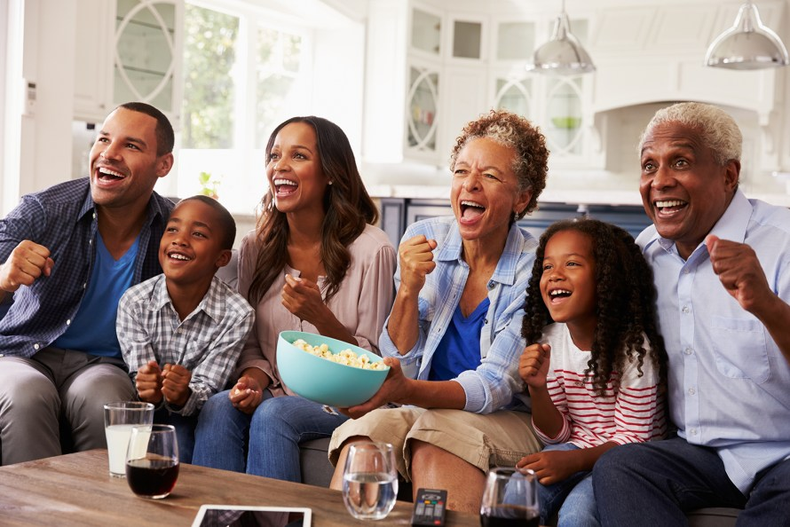 two kids, their parents, and grandparents watching television on a couch