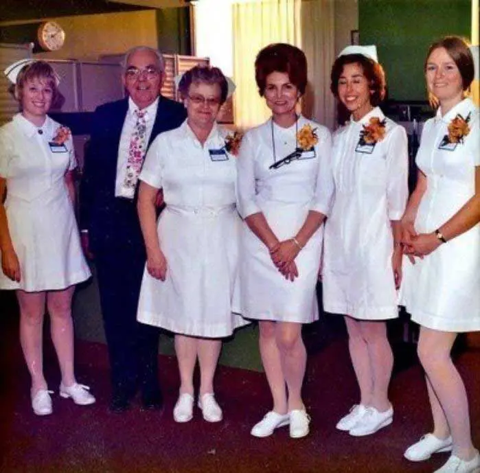 One man and five nurses smiling and standing with each other