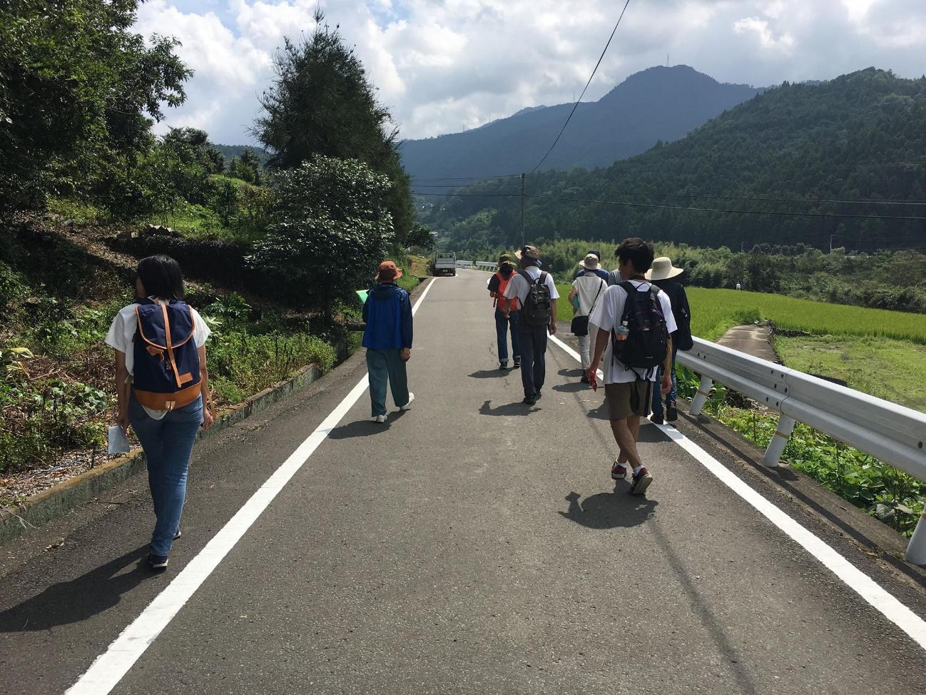 山の中の道を歩く人々  自動的に生成された説明