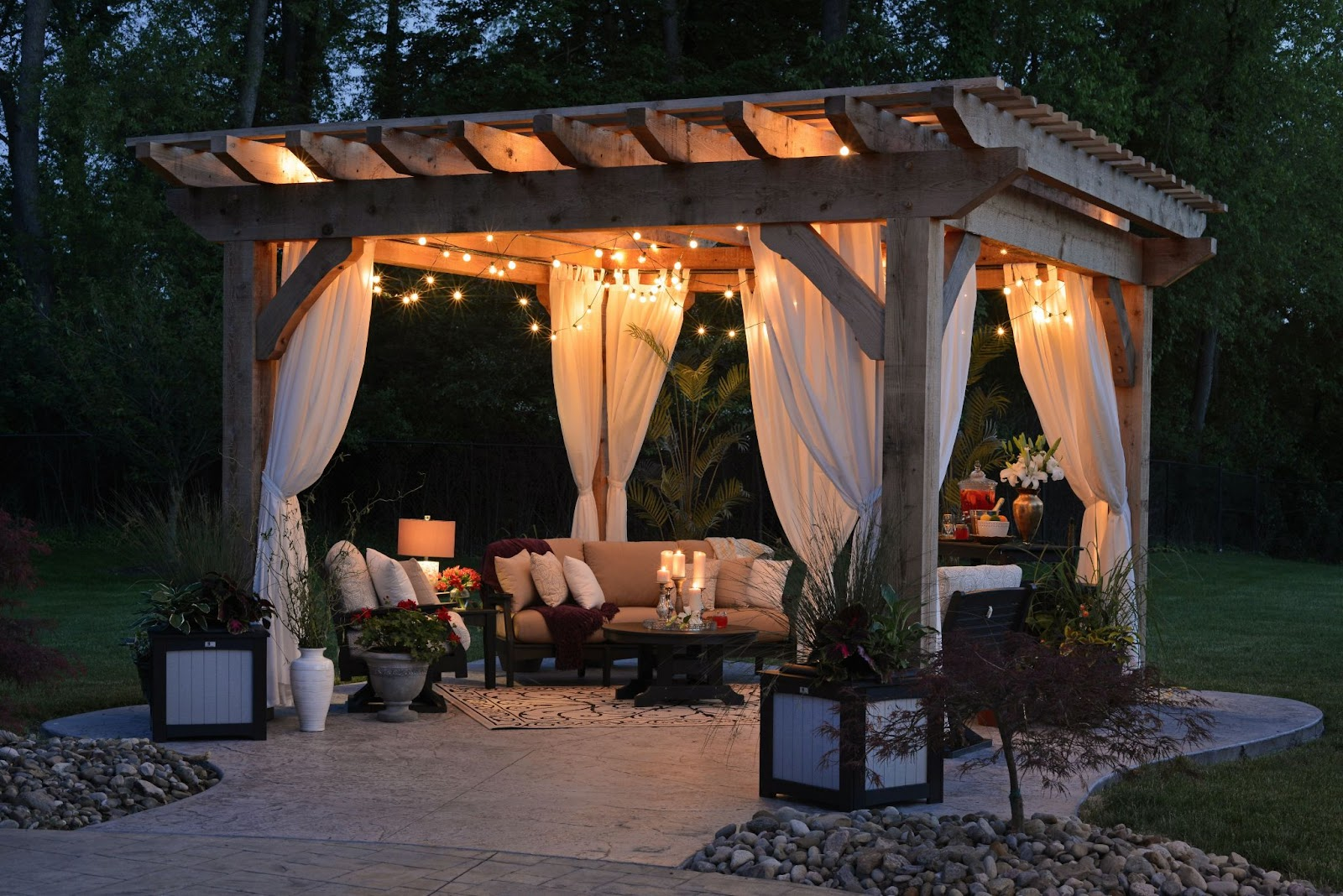 A terrace with sofas, candles, lights in a garden. Cozy environment.