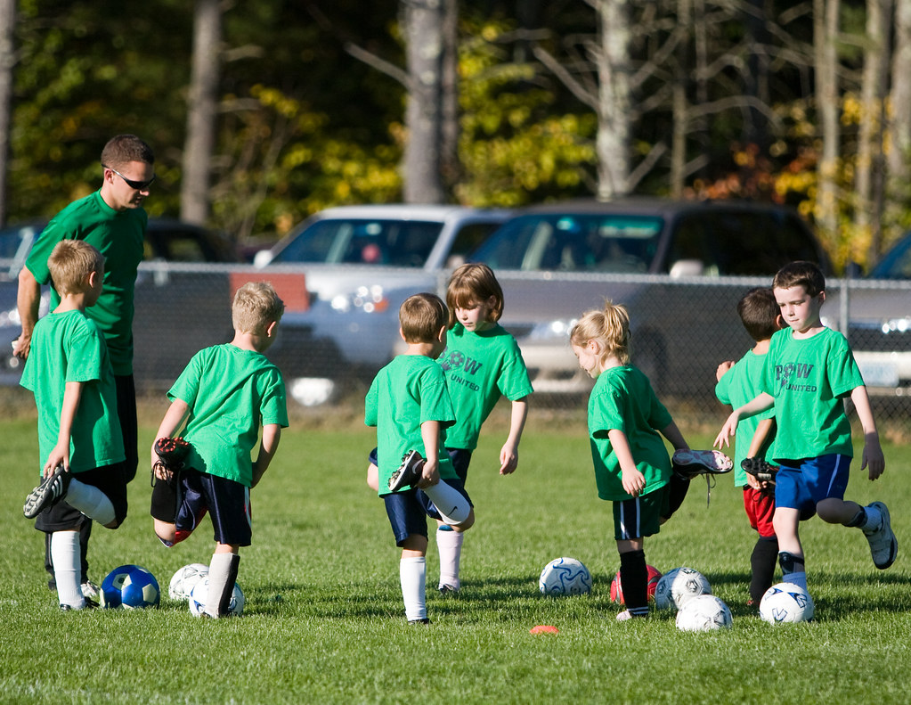 Kids doing stretches with soccer ball and coach  (Soccer for 3 and 4-year-olds)