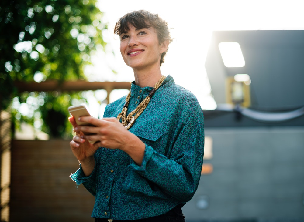 A smiling woman in an azure blouse holding a smartphone while standing outdoors
