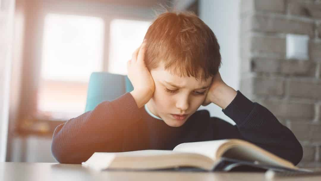 little boy trying to read while covering his ears to block sound