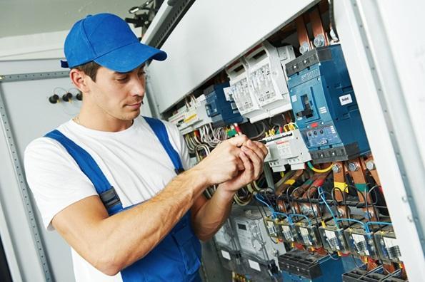 homem-usando-vestimenta-para-trabalhos-com-eletricidade-mexendo-em-uma-caixa-de-luz-com-uma-chave-de-fenda-isolada