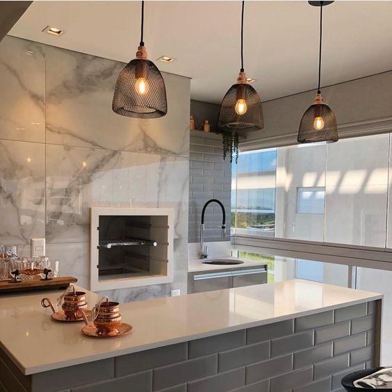 Área gourmet com churrasqueira embutida revestida de porcelanato calacata , bancada com azulejo do metro cinza e superfície de porcelanato branco, lâmpadas pendentes pretas.