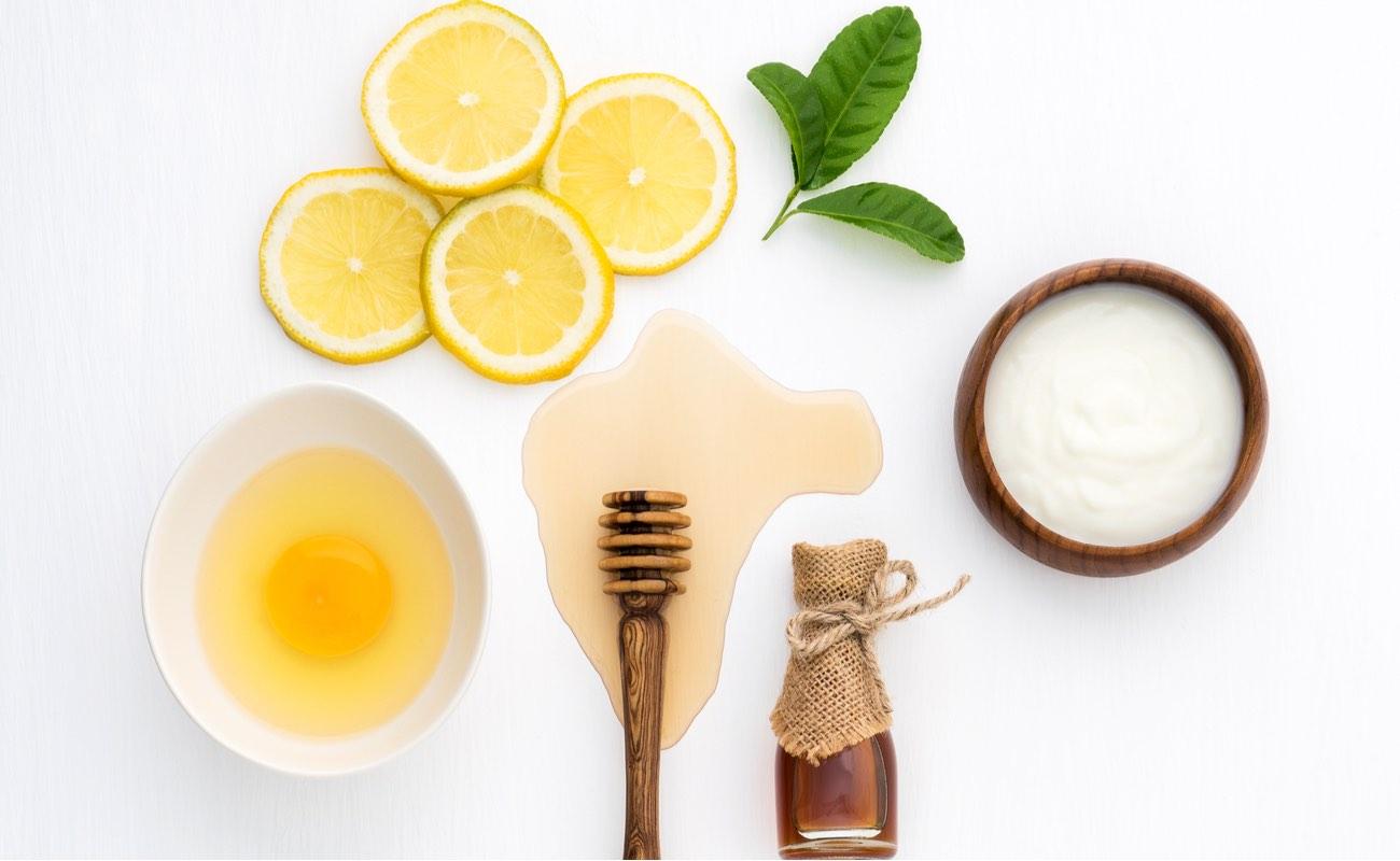 Top view of egg, yoghurt, honey and lemon on white background