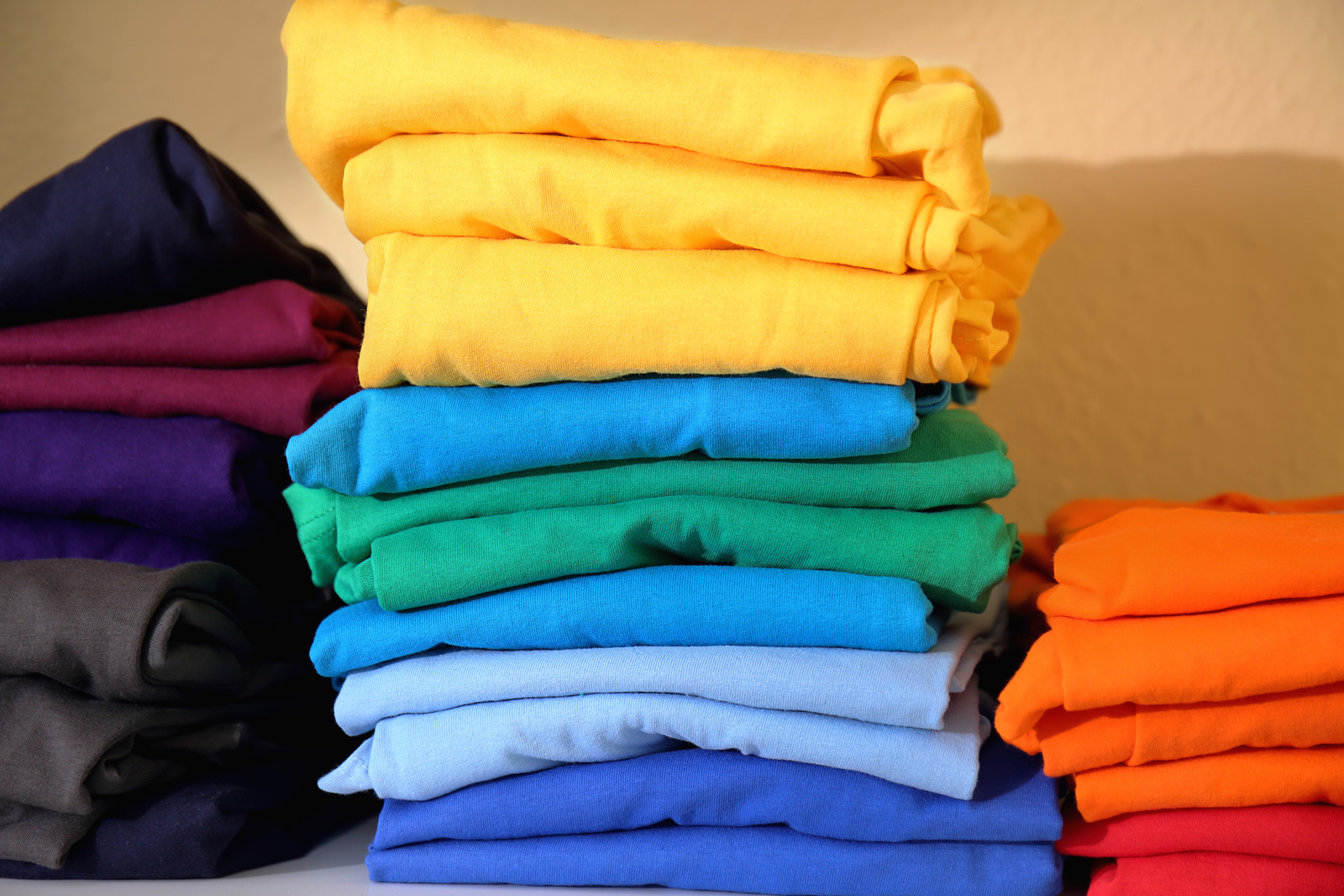 Stacks of Colorful T-Shirts on Shelf
