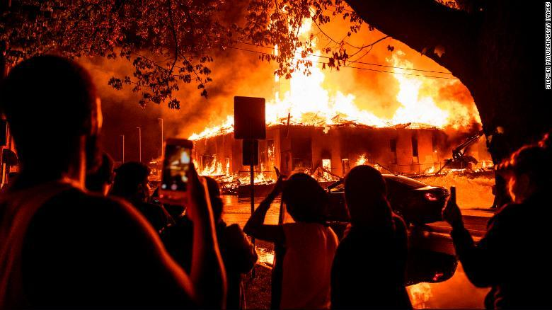 eople look on as a construction site burns in a fire near the 3rd police precinc