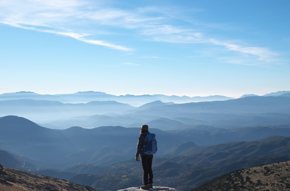 person wearing backpack standing on cliff in front of mountains during daytime