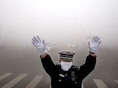 A police officer works on a street blanketed in heavy smog in Harbin on October 21, 2013.