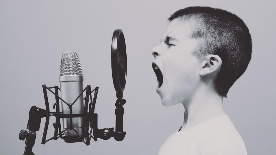 young boy screaming into a microphone
