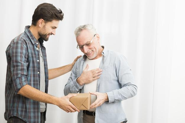 Young guy giving present to aged happy male Premium Photo