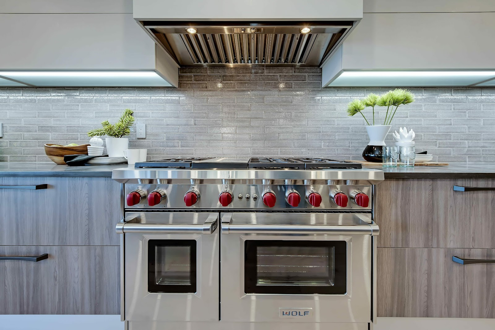 beautiful 6-burner range with hidden hood red knobs centrepiece calgary kitchen design