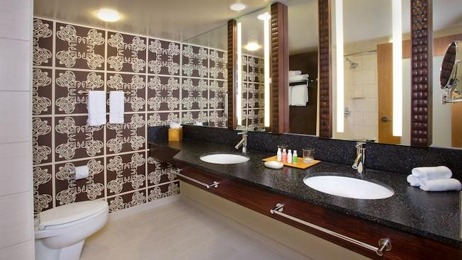 A toilet across from twin sinks sharing a countertop below 4 vertical wall mirrors