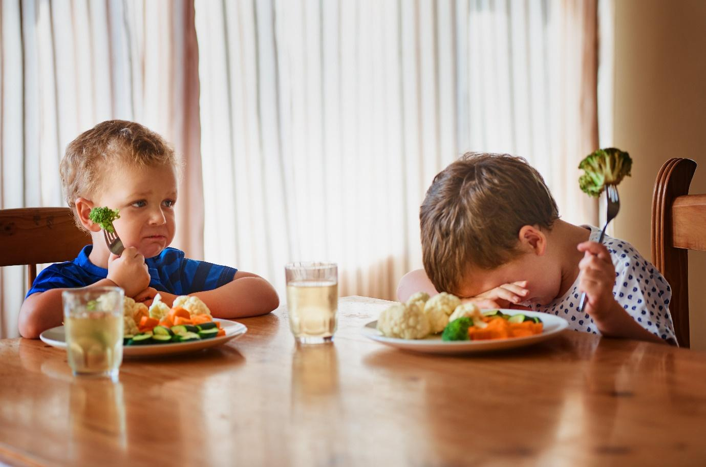 A couple of kids eating at a table  Description automatically generated with low confidence