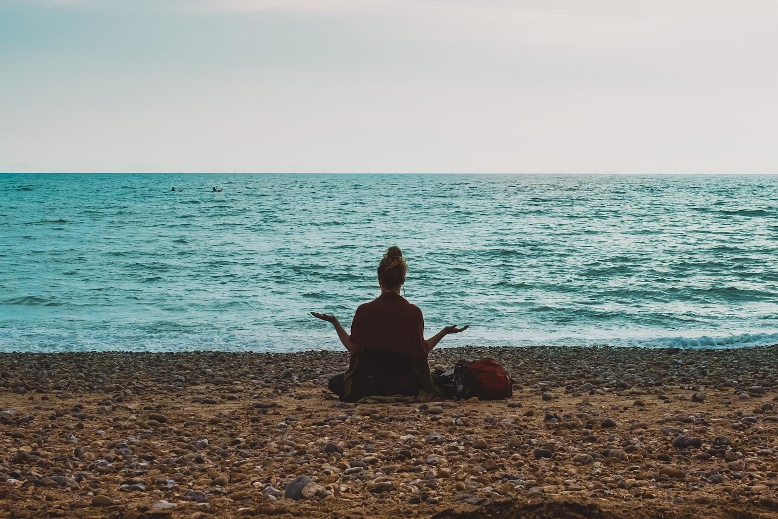 Autoimmune diet: A woman meditates on the beach