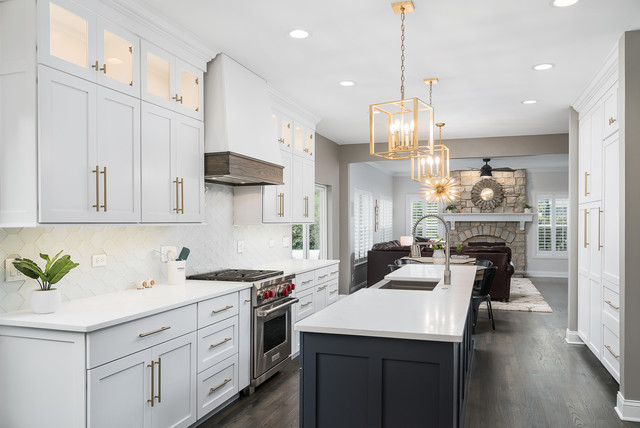 charcoal grey center island with contrasting white shaker cabinets and white countertops. modern brass pendant lighting hangs above