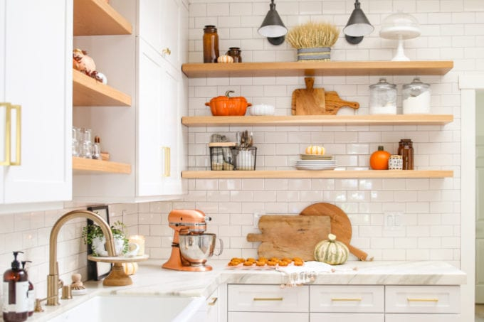 White kitchen with gold fixtures with fall decorations.
