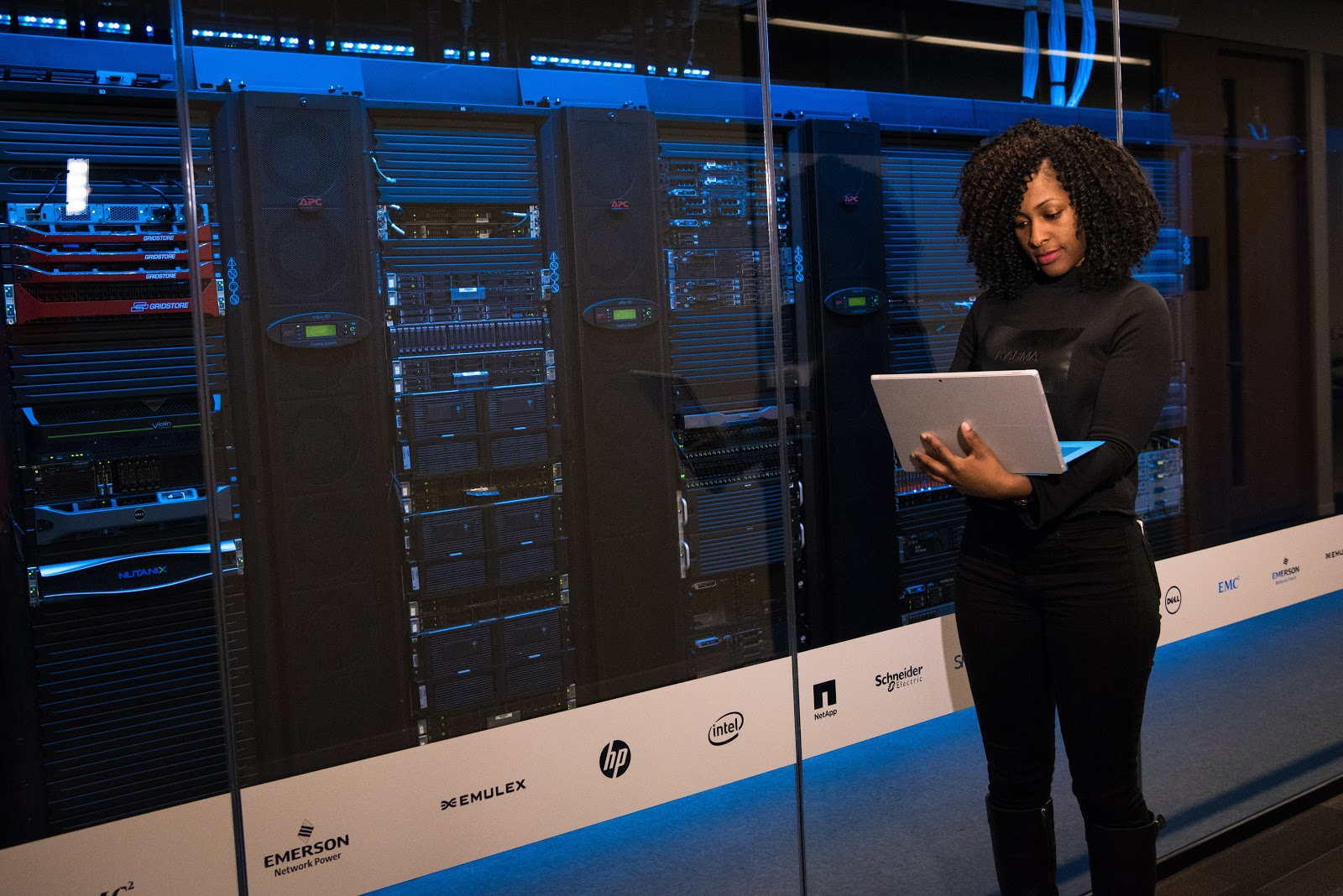 a woman standing next to multiple servers