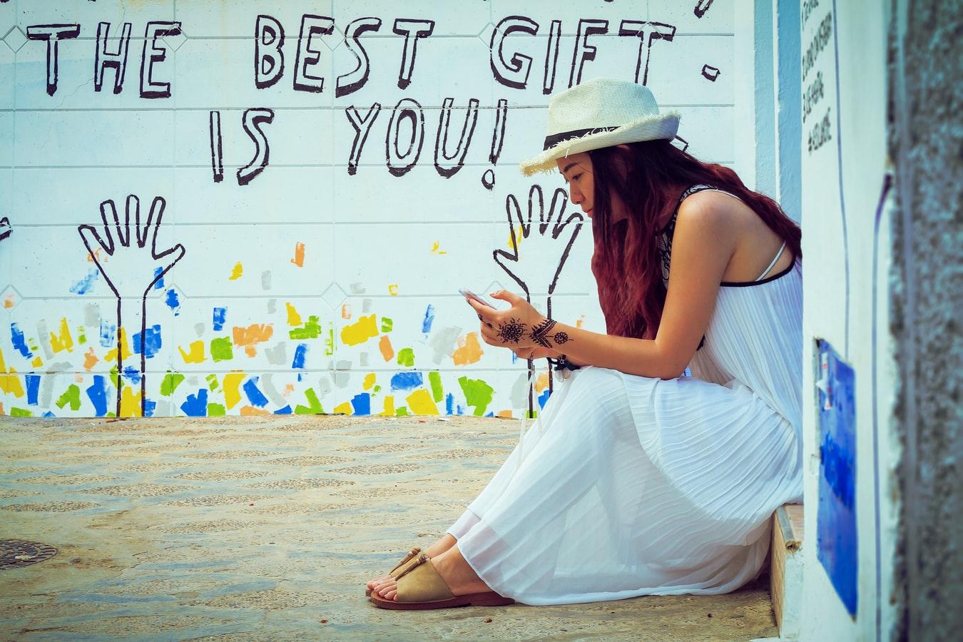 背景以英文寫著:你是世上最美好的禮物。一個戴草帽的白裙女子坐在牆前,側臉微微笑著。
