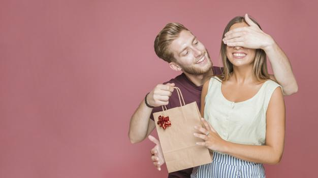 Smiling young man covering her girlfriends eyes holding shopping bag Premium Photo
