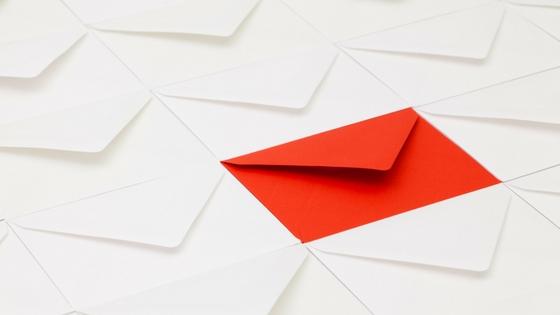 a red envelope among multiple white envelopes