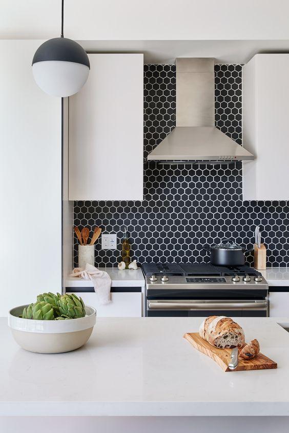 Cozinha em estilo moderno com revestimento hexagonal azul na parede da pia, armários e bancadas brancas com eletrodomésticos de inox.