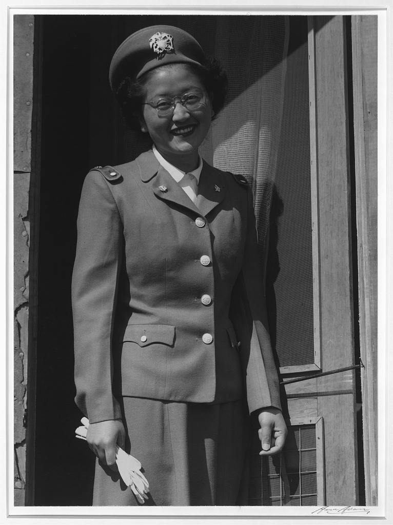 A Japanese American U.S. Naval cadet nurse standing in the doorway of a barrack in Manzanar. She is smiling, wearing her cap and uniform and holding her gloves in one hand.