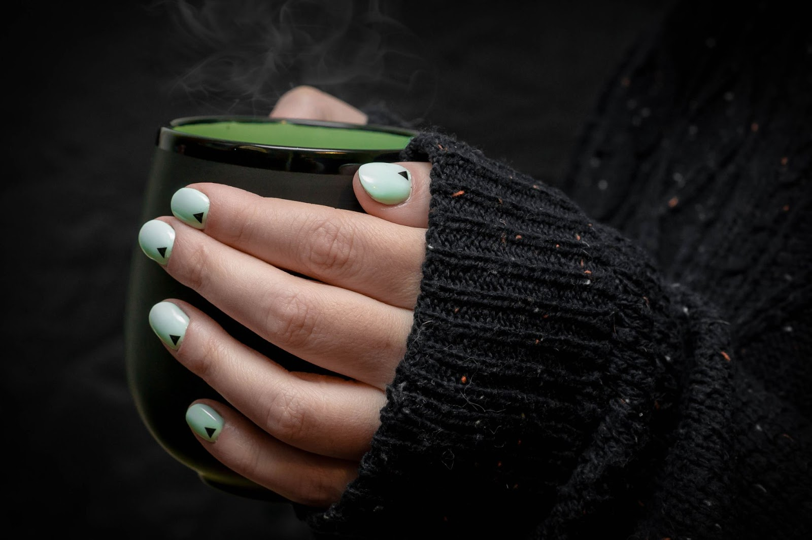 Close up of a green painted finger nails holding a black coffee cup. 'Press on nails' is one of the popular beauty & jewelry keywords on Etsy.