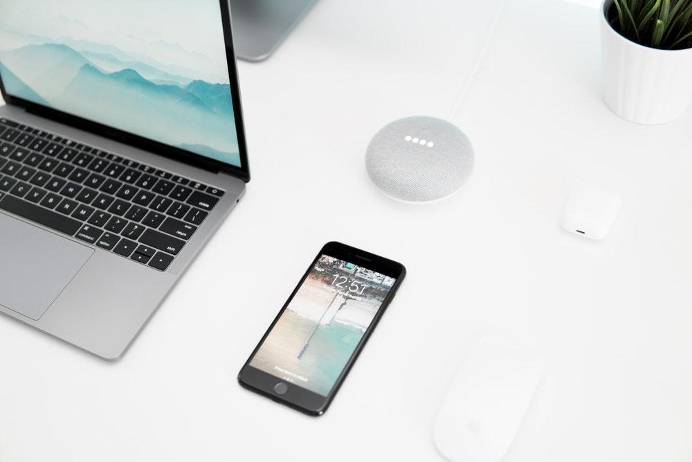 black iPhone 7 beside silver MacBook