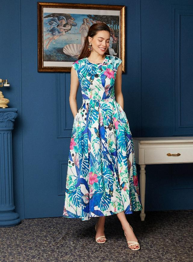 A person in a blue dress standing in front of a window  Description automatically generated