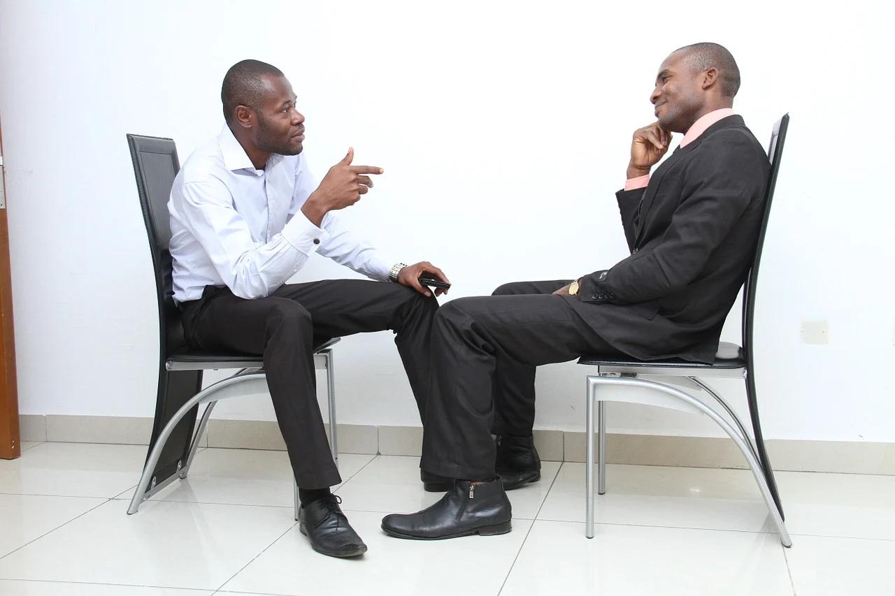 two men talking, sitting