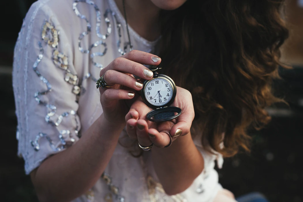 Woman in white shirt holding an old watch